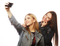 Deux adolescents de sourire prenant la photo avec l'appareil-photo de smartphone Images stock