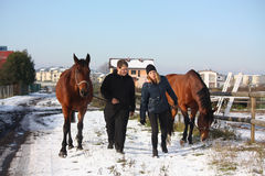 Deux adolescents et deux chevaux marchant dans la neige Images stock