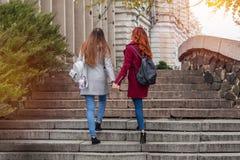Deux adolescents féminins marchant vers le haut des étapes en pierre tenant des mains dedans Image stock