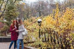 Deux adolescents féminins recherchant les actualités dans le smartphone dans t Photos libres de droits