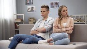 Deux adolescents frustrants s'asseyant sur le divan ont tourné loin, malentendu de querelle photo stock