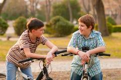 Deux adolescents heureux sur des bicyclettes ayant l'amusement photographie stock