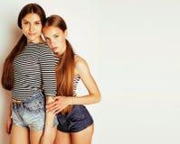 Deux adolescents mignons ayant l'amusement ensemble d'isolement sur le blanc Photographie stock libre de droits