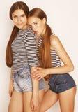 Deux adolescents mignons ayant l'amusement ensemble sur le blanc Image stock