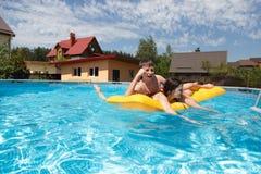 Deux adolescents nageant dans la piscine Photographie stock