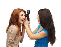 Deux adolescents riants partageant des écouteurs Photographie stock