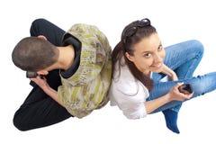 Deux adolescents s'asseyant sur le blanc avec des portables Image stock