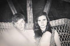 Deux adolescents s'asseyant sur un sof de meubles de rotin Photographie stock libre de droits