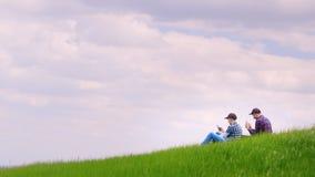 Deux adolescents s'asseyent sur un pré vert, utilisant des téléphones portables Dans la perspective du ciel bleu, a banque de vidéos