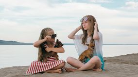 Deux adolescents se reposent sur une plage sablonneuse près de la mer Ils ont deux chiens Photographie stock libre de droits