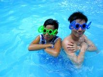 Deux adolescents utilisant des lunettes de soleil avec le mot se refroidissent de son cadre dans une piscine Photographie stock libre de droits