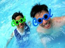 Deux adolescents utilisant des lunettes de soleil avec le mot se refroidissent de son cadre dans une piscine Photos libres de droits