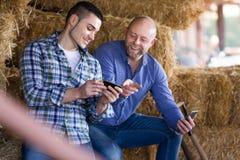 Deux agriculteurs avec des téléphones au grenier à foin Photo libre de droits