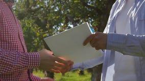 Deux agriculteurs méconnaissables se serrent la main et la préparation pour signer un accord des arbres verts banque de vidéos