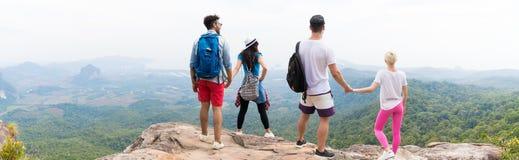 Deux ajouter aux sacs à dos se tenant sur le dessus de montagne apprécient la vue arrière arrière, les jeunes hommes et la femme  Images libres de droits