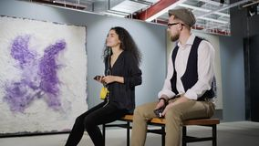 Deux amants d'art apprécient l'illustration moderne dans la galerie et le guide audio de écoute clips vidéos
