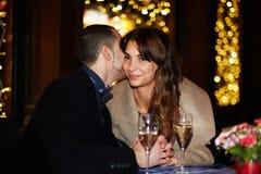 Deux amants s'asseyent chez un homme de restaurant chuchotant des mots doux dans l'oreille de la fille Images libres de droits