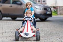 Deux ami heureux ayant l'amusement avec la voiture de jouet Photo libre de droits