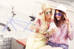 Deux amie à l'aide du smartphone tout en montant la bicyclette tandem Photo stock