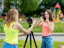 Deux amie Été en nature Écrit la vidéo à l'appareil-photo Gestes avec des mains montrant des pouces  Le concept Photographie stock