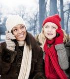 Deux amie aux téléphones dehors en hiver Image libre de droits