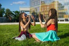 Deux amie avec des dreadlocks de cornrows de zizi donnant la haute cinq entre eux Image stock