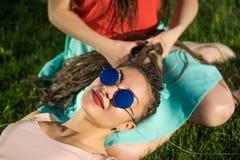 Deux amie avec le dreadlockson de cornrows de zizi verdissent la pelouse Photo libre de droits