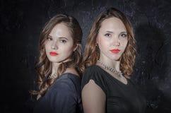 Deux amie beaux se tenant ensemble de nouveau au dos regarder l'appareil-photo Studio tiré dans le style noir Image libre de droits