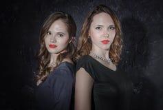 Deux amie beaux se tenant ensemble de nouveau au dos regarder l'appareil-photo Studio tiré dans le style noir Photos stock