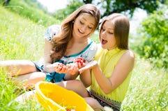 Deux amie dans le plaisir mangeant des fraises Photographie stock libre de droits