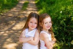 Deux amie de petite fille étreignant dans la forêt Photographie stock libre de droits