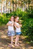 Deux amie de petite fille étreignant dans la forêt Image libre de droits
