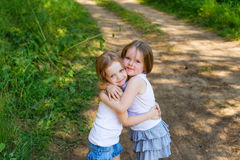 Deux amie de petite fille étreignant dans la forêt Photo stock