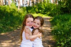 Deux amie de petite fille étreignant dans la forêt Image stock
