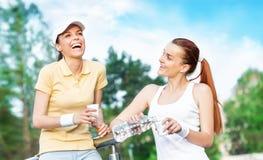 Deux amie de sourire en eau potable d'habillement de sports Photographie stock