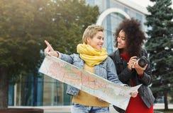 Deux amie dehors avec la carte de papier de ville Photographie stock