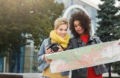 Deux amie dehors avec la carte de papier de ville Image stock