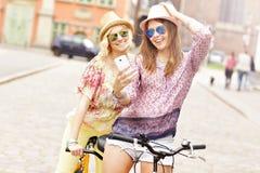 Deux amie heureux montant la bicyclette tandem Photographie stock libre de droits
