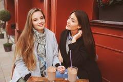 Deux amie heureux parlant et buvant du café dans la ville d'automne en café Images stock