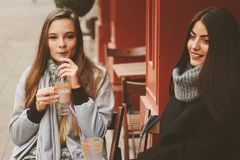 Deux amie heureux parlant et buvant du café dans la ville d'automne en café Réunion de bons amis, jeunes étudiants à la mode Image libre de droits