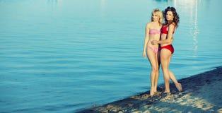 Deux amie posant par le bord de la mer Photo stock