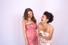 Deux amie riant et ayant l'amusement regardant le téléphone intelligent Technologie, Internet, communication Images stock