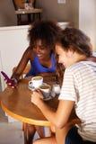 Deux amie s'asseyant au café avec le téléphone portable Images libres de droits