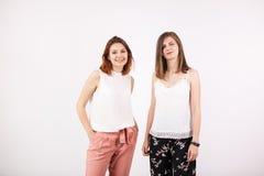 Deux amie souriant sur le mur blanc Images stock