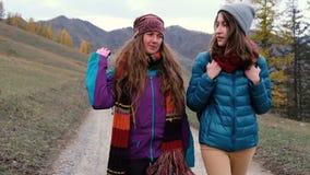 Deux amie trimardant avec le fond de montagnes explorant l'extérieur sauvage ensemble Touristes féminins heureux marchant avec clips vidéos