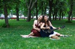 Deux amies élégantes chics de boho heureux avec la guitare, pique-nique Photographie stock