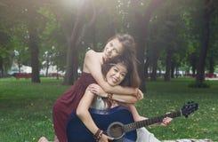 Deux amies élégantes chics de boho heureux avec la guitare, pique-nique Image libre de droits