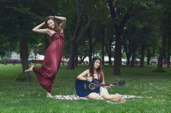 Deux amies élégantes chics de boho heureux avec la guitare, pique-nique Images libres de droits
