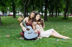 Deux amies élégantes chics de boho heureux pique-niquent en parc Photo stock