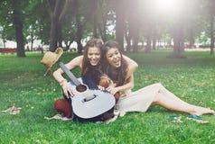 Deux amies élégantes chics de boho heureux pique-niquent en parc Photos libres de droits
